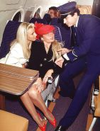Two blondes servicing the captain on an airplane