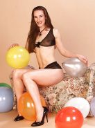 Brunette with small tits naked and plays with balloons