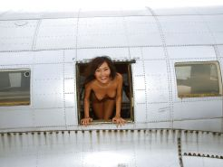 Barefoot naked wife on the wing of an airplane