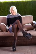 Leggy older blond Jan Burton modelling outdoors in stiletto heels