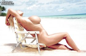 Older blonde pornstar Tiffany Towers exposing huge tits outdoors on beach