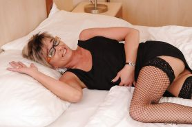 Sassy granny in glasses getting naked and toying her hungry twat