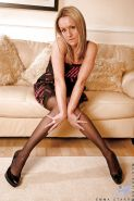 Older blonde MILF Emma Starr modeling non nude on couch in nylons