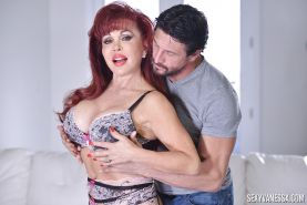 Redheaded pornstar Sexy Vanessa freeing huge fake tits from bra in nylons