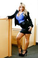 Blonde bombshell Alyssa Lynn with huge fake tits sucking cock at the office