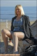 Mature Sandy Spain parting her stockinged legs on the beach and showing pussy