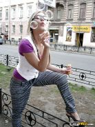 Frisky blonde amateur in glasses showcasing her goods in a public place