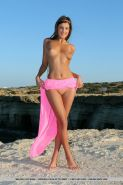 Naked teen Melena A spreading long legs to show shaved pussy on the beach