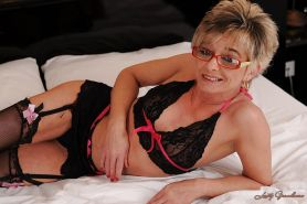 Naughty granny in glasses slipping off her lingerie and spreading her legs