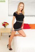 Clothed milf Alina Long is showing off on a bed in her high heels