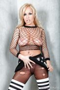 Blonde pornstar Jessica Moore posing in fishnet top and ripped stockings