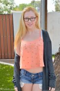 Nerdy teen in glasses and hoodie losing her cutoff denim shorts outdoors