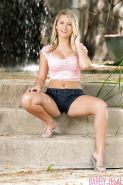 Busty blonde pornstar Chloe Addison posing fully clothed outdoors in shorts