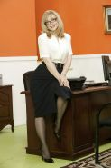 Mature office lady Nina Hartley stripping off her suit and posing in lingerie