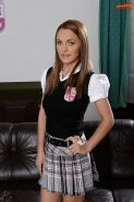 European schoolgirl Dominica Fox modelling fully clothed on leather couch