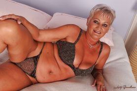 Short haired granny taking off her lingerie and exposing her shaved vag