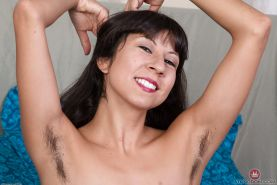 Aged Latina woman Vivi Marie showing off hairy armpits and beaver on bed