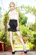 Slender blonde teen in black skirt Piper Perri unclothes outdoors in garden