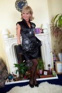 Aged blonde woman Cathy Oakley modeling solo in black gloves and heels