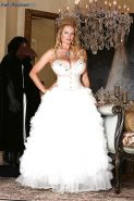 Kelly Madison is posing in a sexy wedding dress and white stockings