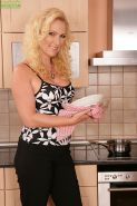 Busty older blond MILF Caroline undressing for nude pictures in the kitchen