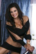 Lusty mature vixen with huge fake tits Teri Weigel stripping on the bed