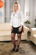 Buxom MILF in stockings Dee Siren stripping off her clothes