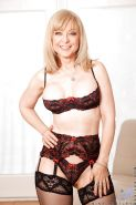 Mature Nina Hartley with big boobs poses in stockings teases her twat