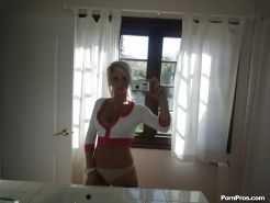 Blonde female Tasha Reign taking mirror self shots while removing her clothes