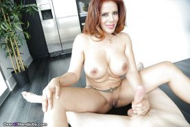 Middle-aged ginger-haired Nicky Ferrari shows off fake tits and jerks dick off