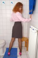 Redhead Claire in stockings posing on the toilet