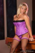 Amber Lynn Bach posing on the pool table in her purple lingerie and stockings