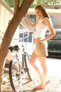 Blonde riding a bicycle on the street and posing