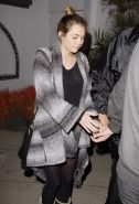 Miley Cyrus braless wearing black see through top outside a restaurant