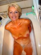 Blonde hairy granny spreads wet mature pussy in the bathtub