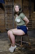 Harley Ace is bound in rope with tits exposed and ass spanked