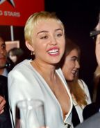 Miley Cyrus braless shows cleavage attending the W Magazine Shooting Stars Exhib