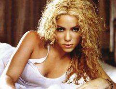 Celeb singer Shakira in red dress and in bed in white cotton