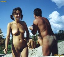 Blonde nudist strips down naked at a public beach