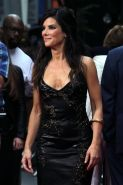 Sandra Bullock braless wearing a low cut leather dress at 'The Heat' premiere in