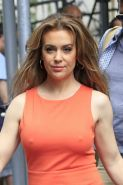 Alyssa Milano braless wearing tight orange mini dress outside the studio in New