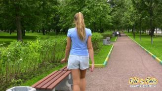 Gal with long ponytail spreading and wetting herself on a garden bench