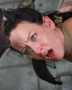 Elise Graves is bound in rope in dungeon and drooling