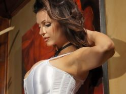 Denise Milani busty showing massive cleavage in sexy white corset at  photoshoot