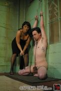 Asian domina practicing cock and ball torture of a tied male
