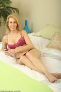 Lingerie wearing older blonde diddles her hairy pussy with a vibrator