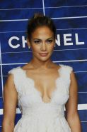 Jennifer Lopez showing big cleavage in a white low cut mini dress at the Chanel
