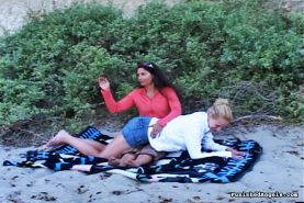 Brunette woman spanking blondes ass at the beach