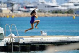 Rosario Dawson shows off her chubby body wearing a purple swimsuit  on the pier