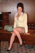 Busty secretary Lorna Morgan in stockings poses in the office